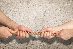 Hände beim Tauziehen als Metapher für einen Konflikt