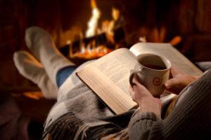 Frau mit Buch und Tasse Kaffee vor dem Kamin